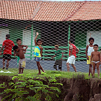 South America, Brazil, Amazon. Young kids of the Amazon pause from their game to watch passing boats.