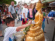 """26 JUNE 2011 - CHIANG MAI, THAILAND:  A boy bathes a statue of the Buddha to """"make merit"""" in the """"Walking Street"""" market in Chiang Mai, Thailand. The Walking Street market is a weekly, Sunday night, market along Ratchadamnoen Street in Chiang Mai.   PHOTO BY JACK KURTZ"""