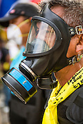 18 FEBRUARY 2014 - BANGKOK, THAILAND:  An anti-government protestor with a gas mask in Bangkok confronts Thai riot police near Government House. Anti-government protestors aligned with Suthep Thaugsuban and the People's Democratic Reform Committee (PDRC) clashed with police Tuesday. Protestors opened fire on police with at rifles and handguns. Police returned fire with live ammunition and rubber bullets. The Bangkok Metropolitan Administration's Erawan Emergency Medical Centre reported that three civilians and a policeman were killed and 64 others were injured in the clashes between police and protesters.   PHOTO BY JACK KURTZ