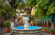 Plaza de San Fernando in Guanajuato, Mexico<br /> ------<br /> Guanajuato is a city and municipality in central Mexico and the capital of the state of the same name. It is part of the macroregion of Bajío. It is in a narrow valley, which makes its streets narrow and winding. Most are alleys that cars cannot pass through, and some are long sets of stairs up the mountainsides. Many of the city's thoroughfares are partially or fully underground. The historic center has numerous small plazas and colonial-era mansions, churches and civil constructions built using pink or green sandstone.<br /> <br /> The origin and growth of Guanajuato resulted from the discovery of minerals in the mountains surrounding it. The mines were so rich that the city was one of the most influential during the colonial period. One of the mines, La Valenciana, accounted for two-thirds of the world's silver production at the height of its production.<br /> <br /> The city is home to the Mummy Museum, which contains naturally mummified bodies that were found in the municipal cemetery between the mid 19th and 20th centuries. It is also home to the Festival Internacional Cervantino, which invites artists and performers from all over the world as well as Mexico. Guanajuato was the site of the first battle of the Mexican War of Independence between insurgent and royalist troops at the Alhóndiga de Granaditas. The city was named a World Heritage Site in 1988.