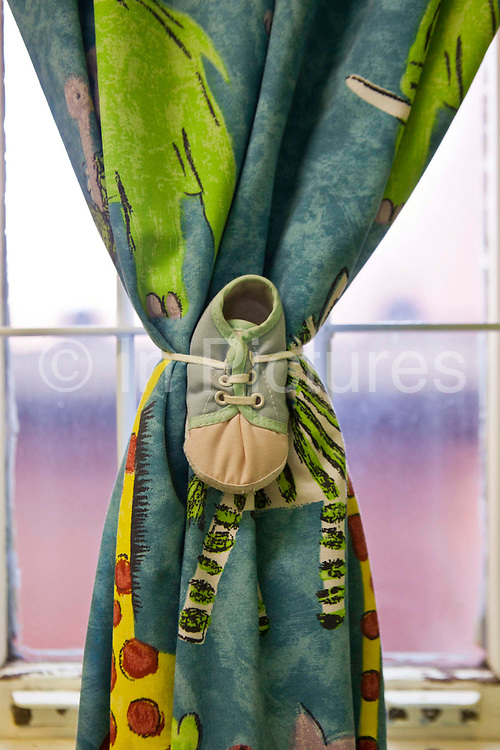 The laces of child's bootie shoe ties together a cartoon-print curtain. Johannesburg, South Africa. It is a curtain at Princess Alice's Adoption home; a children's home in association with BigShoes Foundation.