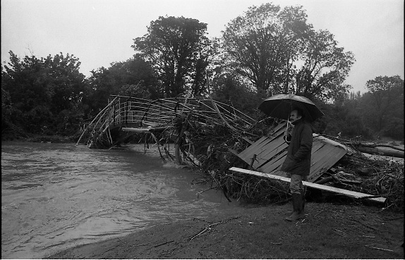 """Flooding at the Dodder..1986..26.08.1986..08.26.1986..28th August 1986..As a result of Hurricane Charly (Charlie) heavy overnight rainfall was the cause of severe flooding in the Donnybrook/Ballsbridge areas of Dublin. In a period of just 12 hours it was stated that 8 inches of rain had fallen. The Dodder,long regarded as a """"Flashy"""" river, burst its banks and caused great hardship to families in the 300 or so homes which were flooded. Council workers and the Fire Brigades did their best to try and alleviate some of the problems by removing debris and pumping out some of the homes affected..Note: """"Flashy"""" is a term given to a river which is prone to flooding as a result of heavy or sustained rainfall...Image of a pedestrian braving the elements as he surveys the damage to the footbridge.Note the size of the trees which were carried by the flood."""