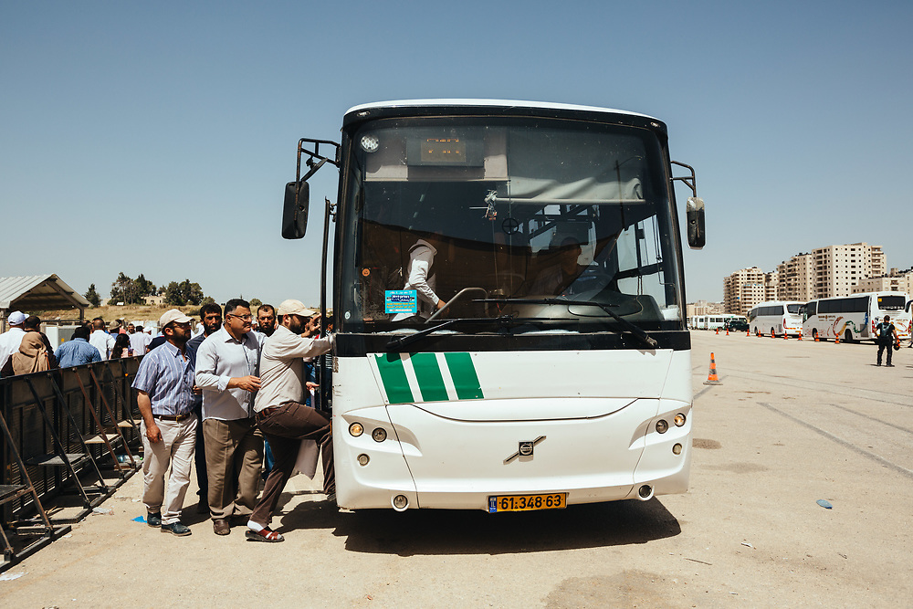 Palestinians board buses headed to Jerusalem after crossing Qalandiya checkpoint, south of Ramallah, West Bank, on May 17, 2019, on their way to perform the second Friday Prayer of the Muslim holy month of Ramadan, at the Al Aqsa Mosque in Jerusalem. Israeli authorities are introducing biometric border crossing systems at West Bank checkpoints, thus minimizing the interaction between Israeli soldiers and Palestinians crossing into Israel.