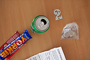 Yorkie bar, Kit Kat, a can of fizzy drink and a bag of coins, on a table numbered 2, in the visitors centre, HMP Kingston. Portsmouth, United Kingdom. Kingston prison is a category C prison holding indeterminate sentenced prisoners.
