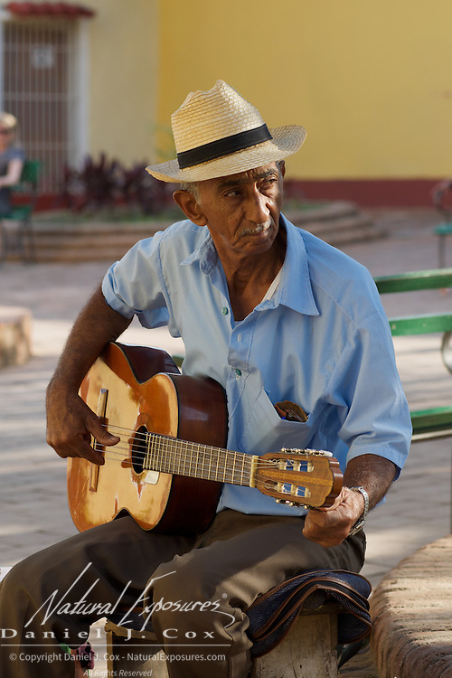 Wakem tunes his guitar in the streets of Trinidad before playing. Cuba.