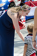 BAR HARBOR, MAINE, July 4, 2014. A marcher in the Independence Day Parade hands candy to a young spectator.