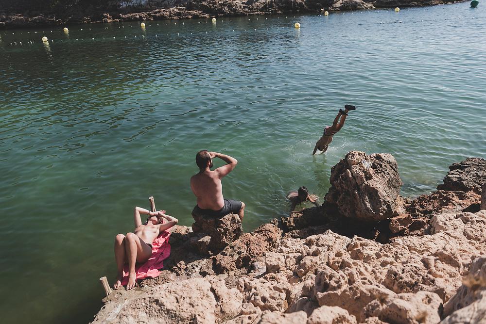 Cala Gració, Ibiza, Spain - July 30, 2018: People enjoy a sunny afternoon on the rocky coastline at Cala Gració, Ibiza.