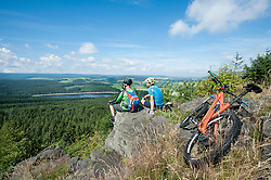 Mountain bikers relaxing on top of mountain, Ore Mountains, Saxony, Germany