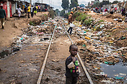 A young boy walks across the rail tracks covered by rotting rubish / trash inside Kibera Slum, Nairobi. Considered to be the largest slum in Africa with a population close to 1 million people. The living conditions in it  are considered of extreme poverty with most housholds having no runing water or sanitation. The population is made up of all ethno-linguistic groups of Kenya drawing many residents from the poorest rural backgrounds.