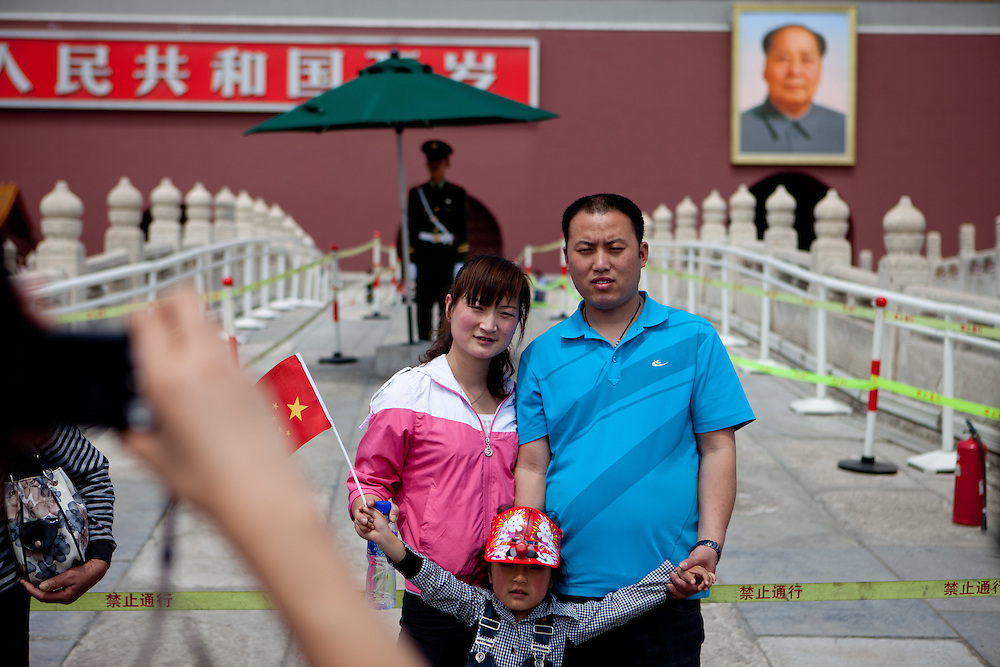 """A family is getting photographed at the main gate of """"The Forbidden City"""" which was the Chinese imperial palace from the Ming Dynasty to the end of the Qing Dynasty. It is located in the middle of Beijing, China. Beijing is the capital of the People's Republic of China and one of the most populous cities in the world with a population of 19,612,368 as of 2010."""