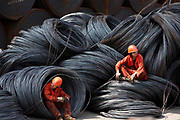 Workers take a break while sitting on a pile of steel wires at a stockyard run by the Shanghai Yirong Trading Company Ltd in Shanghai, China on 10 April 2009.