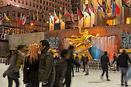 Night ice Skaters at Rockefeller Center Ice Rink, with focus on golden Statue of Prometius in background,  in Manhattan, New York, USA, on January 9, 2012