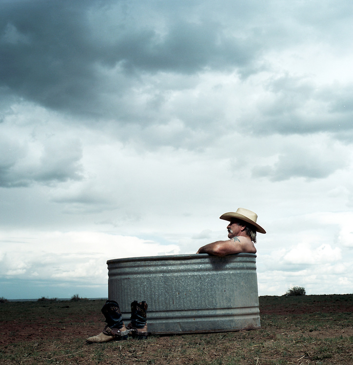 60's older cowboy sitting in water tank on a horse pasture.