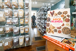 Book on Spice Blends and shopper on aisle with racks full of chiles and spices at Pendery's World of Chiles & Spices retail store, Fort Worth, Texas USA.