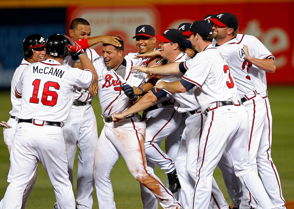 ATLANTA - JUNE 30:  Teammates mob second baseman Martin Prado #14 of the Atlanta Braves (fourth from the left) after his game winning hit in the bottom of the 10th inning during the game against the Philadelphia Phillies at Turner Field on June 30, 2009 in Atlanta, Georgia.  The Braves beat the Phillies 5-4 in 10 innings.  (Photo by Mike Zarrilli/Getty Images)