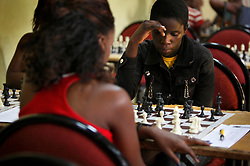 Phiona Mutesi, right, a 14-year-old chess prodigy, plays chess in Kampala, Uganda, Dec. 11, 2010. Mutesi lives in the slums of Uganda and is just now learning to read. But her instincts have made her a player to watch in international chess. Mutesi, a naturally talented chess player is coached by Robert Katende of Sports Outreach Ministry. The chess club meets at the Agape Church inside Katwe, the largest slum in Kampala.
