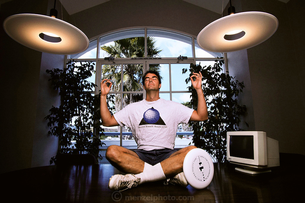 Silicon Valley, California; Timothy C. Draper, 3rd generation venture capitalist, at and on the conference room table of his offices in Redwood City. He plays competitive Frisbee. Model Released (1999).