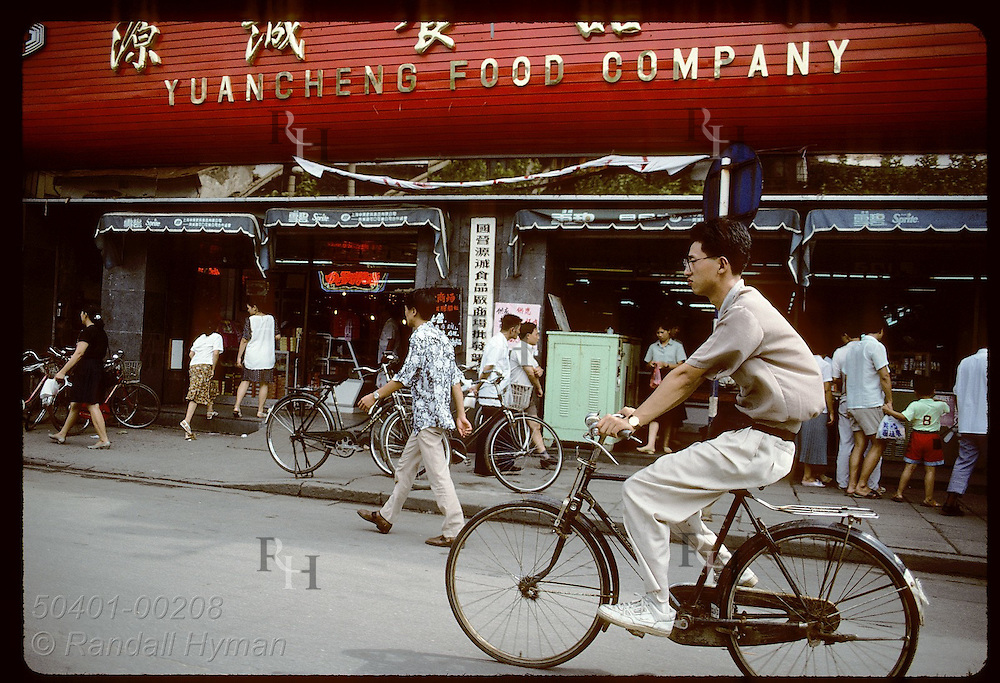 Young man rides his bike past a supermarket on a main street in downtown Shanghai. China