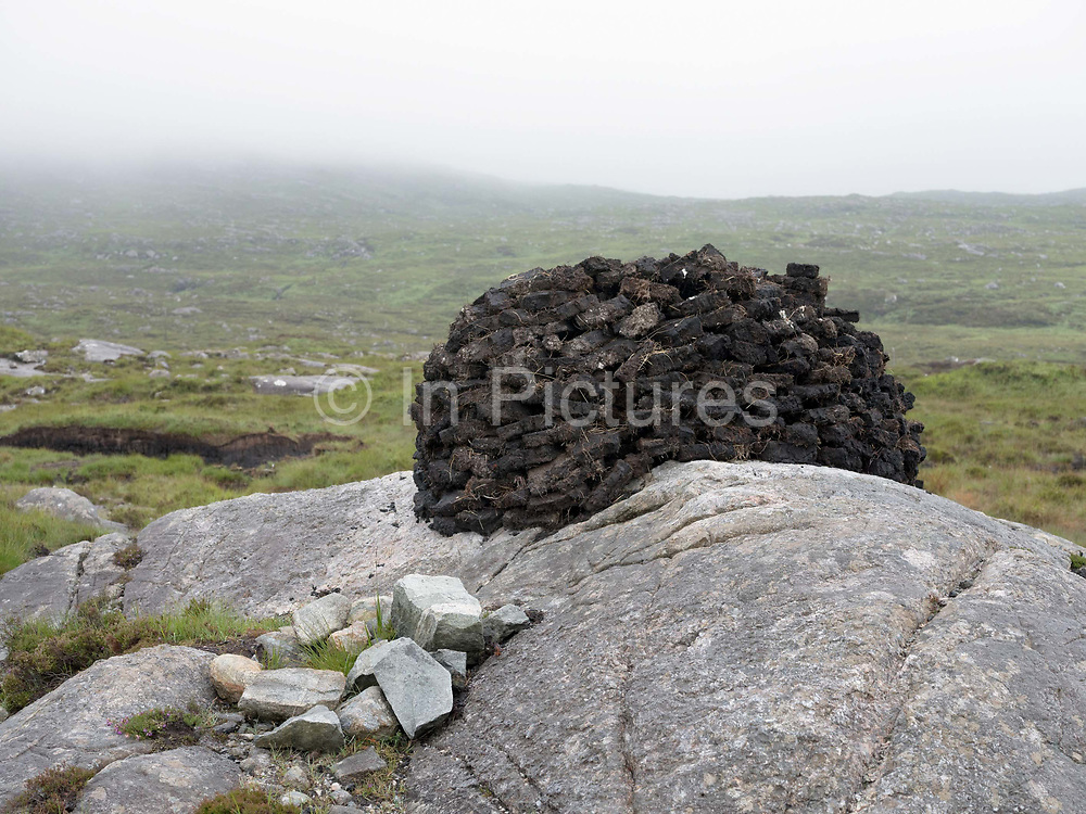 A pile of freshly cut peat to be used for fuel on the Isle of Harris, Outer Hebrides, Scotland on 15th July 2018. Turbary is the ancient right to cut turf, or peat, for fuel on a particular area of bog