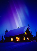 Auroral rays at dawn over cabin on the shore of Colorado Lake, geomagnetic storm on March 31, 2001, Broad Pass, Alaska.