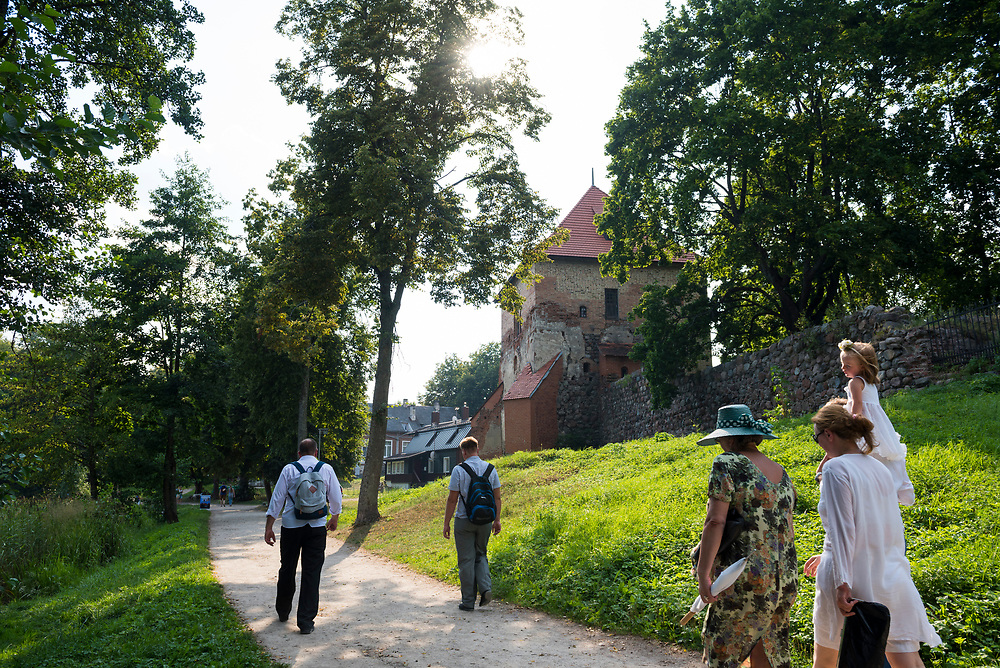 Trakai, Lithuania - August 8, 2015: People walk down a dirt path on a summer afternoon in Trakai, Lithuania. The town, best known for its picturesque red-brick castle (not pictured), is located 28 kilometers from Vilnius.