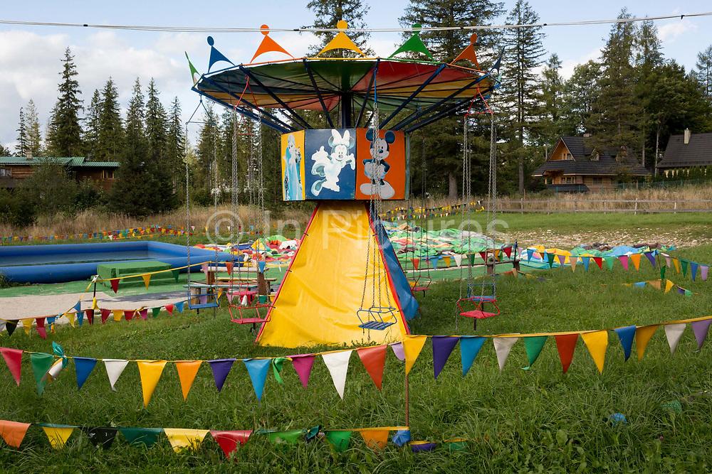 A landscape of a Polish version of Disneyland that features a childrens merry-go-round carousel, on 18th September 2019, near the Wielka Krokiew ski jump, Zakopane, Malopolska, Poland.