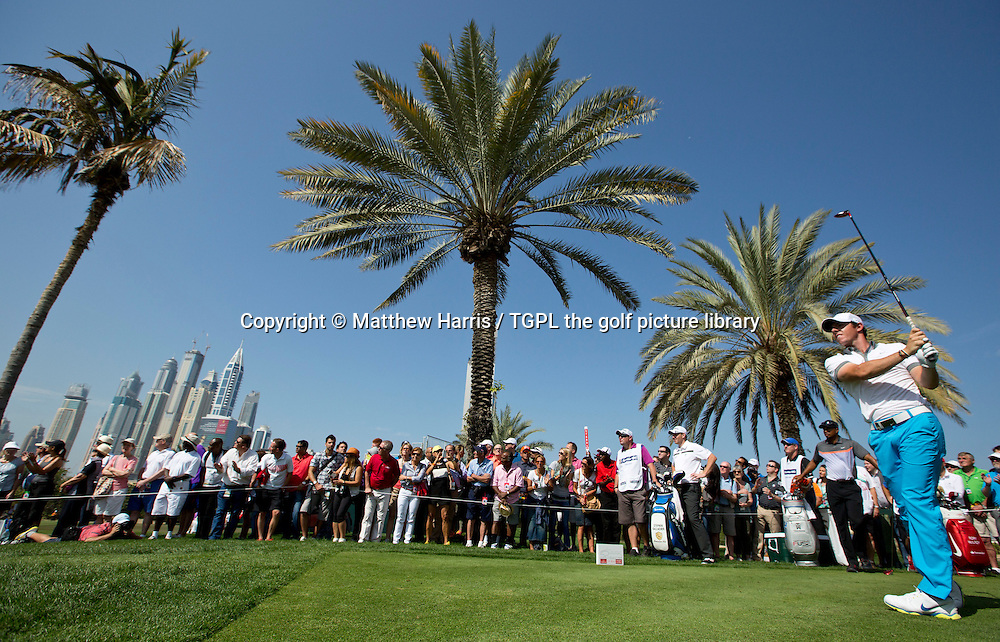 Rory MCILROY (NIR) tees off the 9th as city and palm trees blend and Tiger WOODS (USA) and Stephen GALLAGHER (SCO) look on during first round  Omega Dubai Desert Classic 2014, Emirates Club,Dubai,UAE.