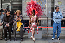 © licensed to London News Pictures. London, UK 12/05/2013. A dancer with carnival dress, representing Trinidad and Tobago, resting at a bus stop at The World on Regent Street event in London on Sunday, 12 May 2013. Many countries showcase the best of each country's culture, music and dance, art, food and fashion to Londoners on Regent Street. Photo credit: Tolga Akmen/LNP