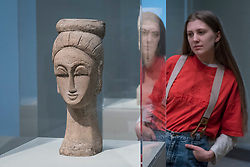"""© Licensed to London News Pictures. 21/11/2017. London, UK.  A staff member views a sculpture called """"Woman's Head (with Chignon)"""", 1911-12.  """"Preview of """"Modigliani"""", the most comprehensive exhibition of works by Amedeo Modigliani ever held in the UK.  On display are iconic portraits, sculptures and 12 nudes, the largest group ever shown in the UK.  The show runs 23 November to 2 April 2018. Photo credit: Stephen Chung/LNP"""
