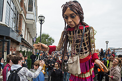 Little Amal, a giant puppet of a Syrian refugee girl fleeing conflict, gives a high five to a boy outside the Globe Theatre on 23rd October 2021 in London, United Kingdom. The 3.5-metre puppet, which is nearing the end of an 8,000km journey from the Turkish-Syrian border to Manchester in support of refugees, earlier climbed the steps of St Paul's Cathedral to present a wood carving of a ship at sea from St Paul's birthplace at Tarsus in Turkey to the dean.