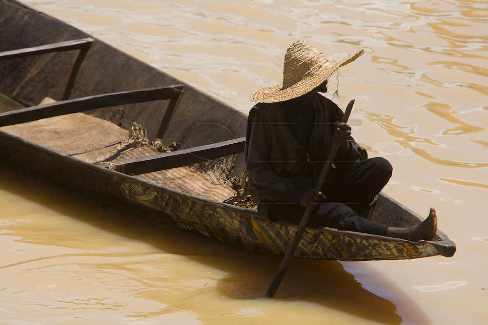 """A man drives a """"pinasse"""" in the harbour of Mopti. At the confluence of the Niger and the Bani rivers, between Timbuktu and Ségou, Mopti is the second largest city in Mali, and the hub for commerce and tourism in this west-african landlocked country."""