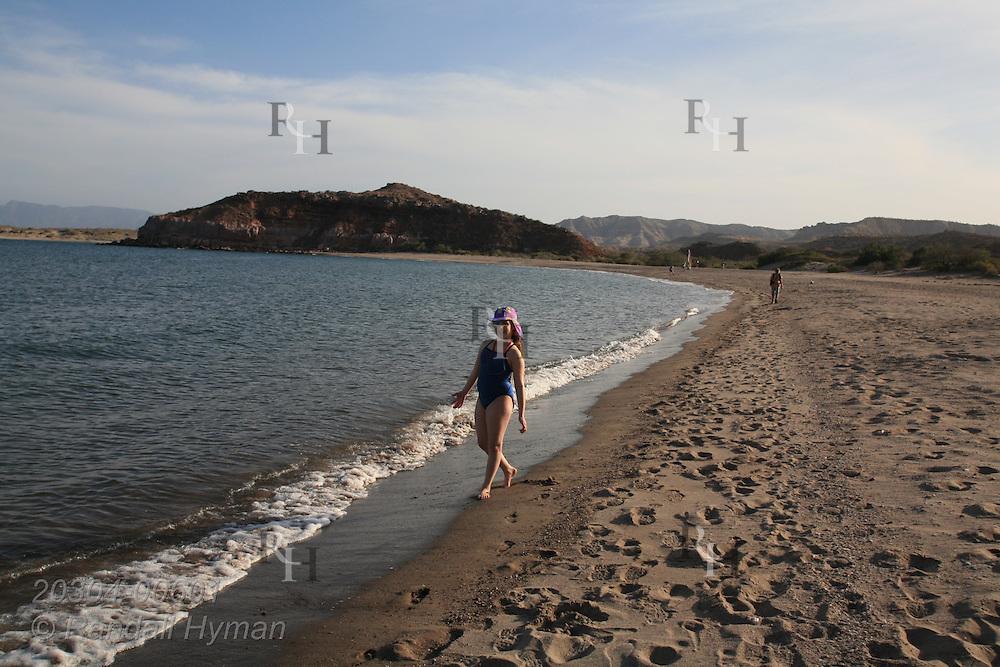 Young girl walks along Sea of Cortez beach at Puerto Gato; Baja, Mexico.