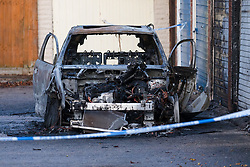 © Licensed to London News Pictures. 20/11/2019. London, UK. A burnt out car at garages near the crime scene at Owen Waters House in Fullwell Avenue, Ilford where a 19 year old man died after suffering stab injuries last night. Police were called at 22:20 on 19th November following reports of a fight outside Owen Waters House where they attended to a 19 year old man suffering from stab injuries, who died at the scene.  Photo credit: Vickie Flores/LNP