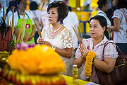 17 OCTOBER 2012 - BANGKOK, THAILAND:  Women pray at a temporary shrine set up for the Vegetarian Festival on Yaowarat Road in Bangkok's Chinatown. The Vegetarian Festival is celebrated throughout Thailand. It is the Thai version of the The Nine Emperor Gods Festival, a nine-day Taoist celebration celebrated in the 9th lunar month of the Chinese calendar. For nine days, those who are participating in the festival dress all in white and abstain from eating meat, poultry, seafood, and dairy products. Vendors and proprietors of restaurants indicate that vegetarian food is for sale at their establishments by putting a yellow flag out with Thai characters for meatless written on it in red.       PHOTO BY JACK KURTZ
