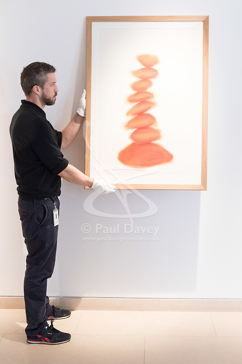 """Christies, St James, London, March 4th 2016. A gallery technician hangs David Nash's """"Column"""", pastel on paper, created especially for the auction at the preview for the It's Our World charity auction at Christie's. Over 40 leading artists including David Hockney, Sir Antony Gormley, David Nash, Sir Peter Blake, Yinka Shonibare, Sir Quentin Blake, Emily Young and Maggi Hambling have committed artworks to the It's Our World Auction in support of The Big Draw and Jupiter Artland Foundation, to be sold at Christie's London on 10 March 2016.<br />  ///FOR LICENCING CONTACT: paul@pauldaveycreative.co.uk TEL:+44 (0) 7966 016 296 or +44 (0) 20 8969 6875. ©2015 Paul R Davey. All rights reserved."""