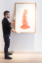 "Christies, St James, London, March 4th 2016. A gallery technician hangs David Nash's ""Column"", pastel on paper, created especially for the auction at the preview for the It's Our World charity auction at Christie's. Over 40 leading artists including David Hockney, Sir Antony Gormley, David Nash, Sir Peter Blake, Yinka Shonibare, Sir Quentin Blake, Emily Young and Maggi Hambling have committed artworks to the It's Our World Auction in support of The Big Draw and Jupiter Artland Foundation, to be sold at Christie's London on 10 March 2016.<br />  ///FOR LICENCING CONTACT: paul@pauldaveycreative.co.uk TEL:+44 (0) 7966 016 296 or +44 (0) 20 8969 6875. ©2015 Paul R Davey. All rights reserved."