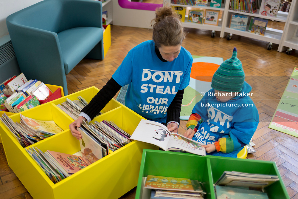 Young reader and his mum in the re-opened Carnegie Library on Herne Hill in south London which has opened its doors for the first time in almost 2 years, on 15th February 2018, in London, England. Closed by Lambeth council and occupied by protesters for 10 days in 2016, the library bequeathed by US philanthropist Andrew Carnegie has been locked ever since because, say Lambeth austerity cuts are necessary. A gym that locals say they don't want or need has been installed in the listed basement and actual library space a fraction as before and it's believed no qualified librarians will be present to administer it. Protesters also believe this community building will ultimately sold off by Lambeth council for luxury homes.
