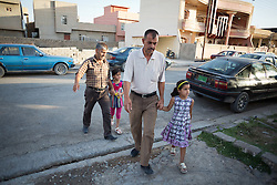© Licensed to London News Pictures. 27/07/2014. Hamdaniyah, Iraq. Rania Minowar Salim (9), an Iraqi Christian refugee from Mosul, walks to church with her father, Ra'id Samir Kamal (45), in Hamdaniyah, Iraq.<br /> <br /> Having taken over Mosul Iraq's second largest city in June 2014, fighter of the Islamic State (formerly known as ISIS) have systematically expelled the cities Christian population. Despite having been present in the city for more than 1600 years, Christians in the city were given just days to either convert to Islam, pay a tax for being Christian or leave; many of those that left were also robbed at gunpoint as they passed through ISIS checkpoints. Photo credit: Matt Cetti-Roberts/LNP