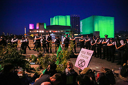 London, UK. 20th April 2019. Large numbers of police officers stand around climate change campaigners from Extinction Rebellion on Waterloo bridge as part of an operation to try to clear the bridge of activists and visitors. The bridge has now been blocked throughout the six days of the International Rebellion called by Extinction Rebellion to demand urgent action to combat climate change by the British government.