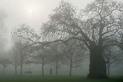 © Licensed to London News Pictures. 01/04/2014. Hammersmith, UK . A jogger runs throughout the fog. A foggy morning in Ravenscourt Park in Hammersmith West London today April 1st 2014. Photo credit : Stephen Simpson/LNP