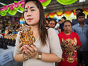 20 SEPTEMBER 2015 - SARIKA, NAKHON NAYOK, THAILAND:  A woman holds a statue of Ganesha at the Ganesh festival at Shri Utthayan Ganesha Temple in Sarika, Nakhon Nayok. Ganesh Chaturthi, also known as Vinayaka Chaturthi, is a Hindu festival dedicated to Lord Ganesh. Ganesh is the patron of arts and sciences, the deity of intellect and wisdom -- identified by his elephant head. The holiday is celebrated for 10 days. Wat Utthaya Ganesh in Nakhon Nayok province, is a Buddhist temple that venerates Ganesh, who is popular with Thai Buddhists. The temple draws both Buddhists and Hindus and celebrates the Ganesh holiday a week ahead of most other places.   PHOTO BY JACK KURTZ