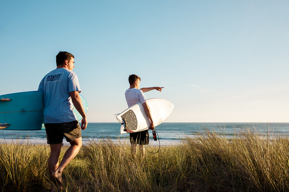 Men holding surfboards, walking through the sand dunes towards the sunset and watching the sirf and waves breaking at St Ouen's Bay, Jersey, Channel Islands