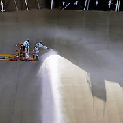 two workers spray painting a ship