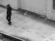 A pedestrian leaves tracks during a snow flurry in Alexandria, Virginia.