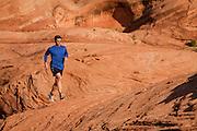 One man trail running at dawn on the Bartlett Wash trail near Moab Utah