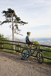 Mountain biker resting while sitting on wooden railing