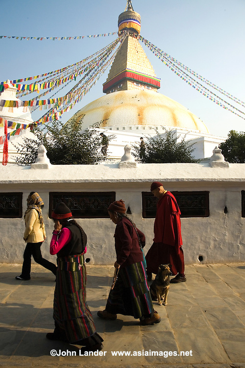 """Boudhnath stupa is the largest in Nepal. Its massive white dome looms over concentric ascending terraces. There are 108 images of the Buddha set around the base of the stupa. Tibetan Buddhist monasteries are scattered all around and a large Tibetan community resides in the area, who make their daily """"kora"""" circling the stupa, twirling prayer wheels as they pass.  UNESCO has declared Bouddhanath a World Heritage Site."""