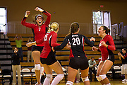 Olivia Wilks '12, left, celebrates with her teammates after the Pioneers scored the final winning point of Saturday's five-set victory over Lake Forest College in Darby Gymnasium.