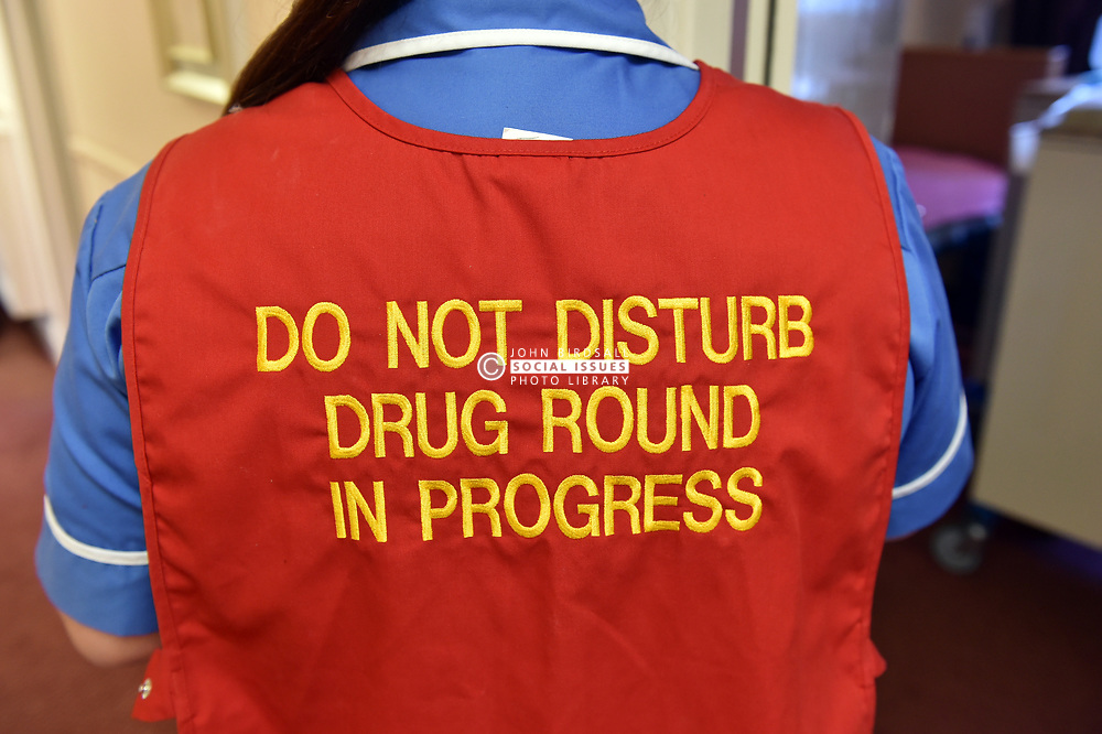 Staff in a care home dispenses drugs wearing a 'Do Not Disturb' tabard UK