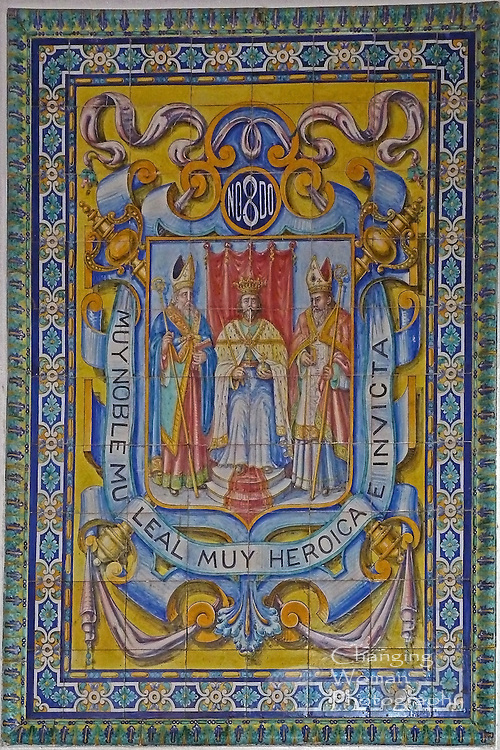 """Vintage Spanish tile mural adorns a wall on the top floor of the Hotel Sevilla, Havana, Cuba.  Its image features iconic heraldry associated with the city of Seville, Spain: a seated monarch, King Ferdinand III (San Fernando Rey), flanked by two religious leaders, Saints Leander and Isadore, is surrounded by the motto, """"Muy noble muy leal muy heroica e invicta"""" (""""most noble, most loyal, most heroic and invincible"""")."""